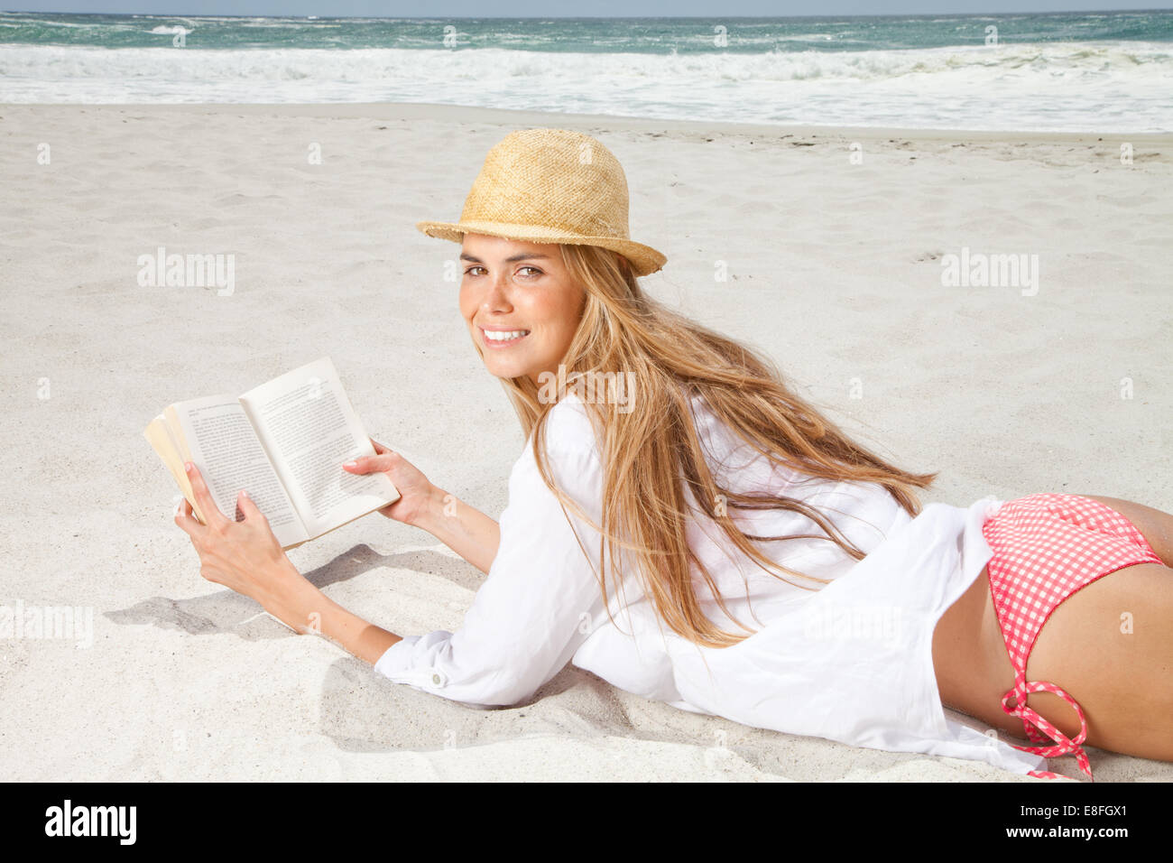 Woman lying on beach reading a book - Stock Image