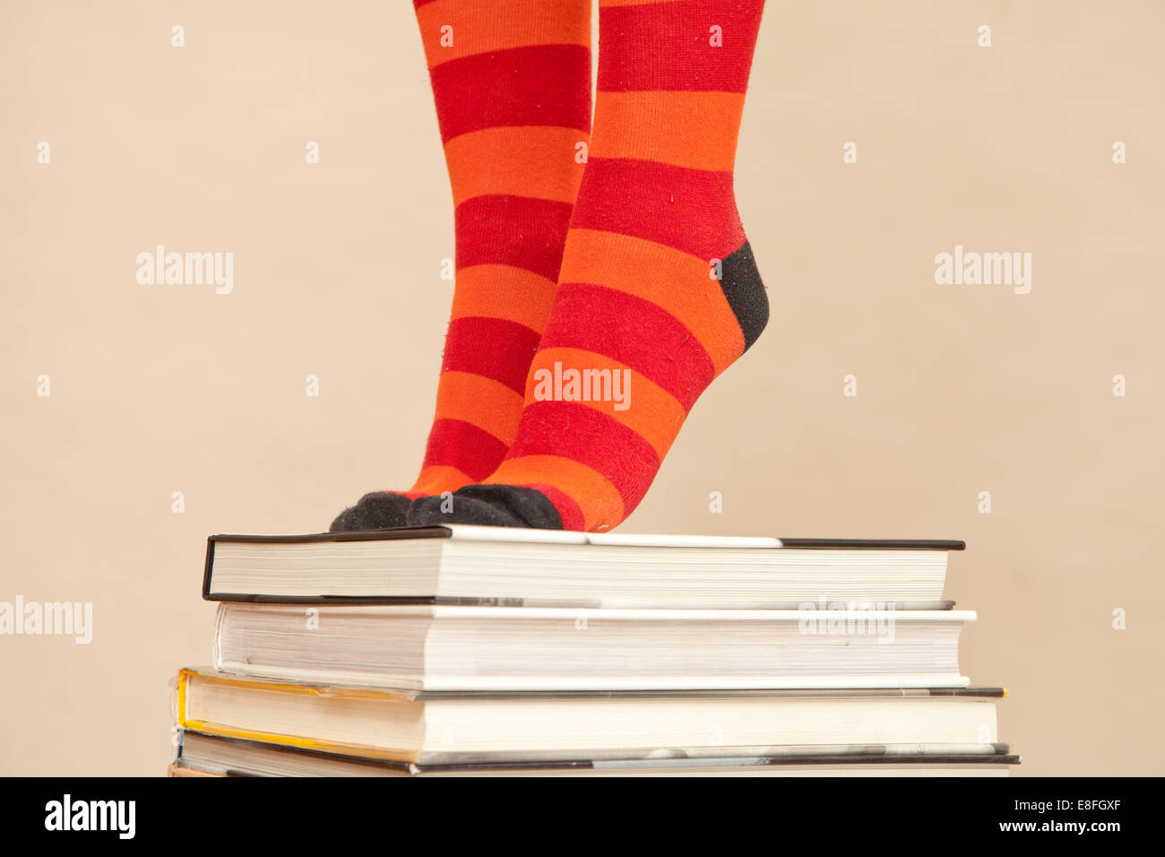 Woman's Feet in stripy socks standing on stack of books - Stock Image