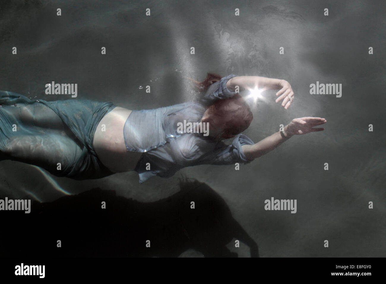 Fully clothed Pregnant woman swimming underwater - Stock Image