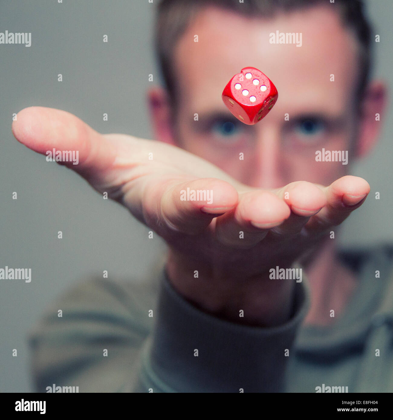 Man throwing dice in air - Stock Image