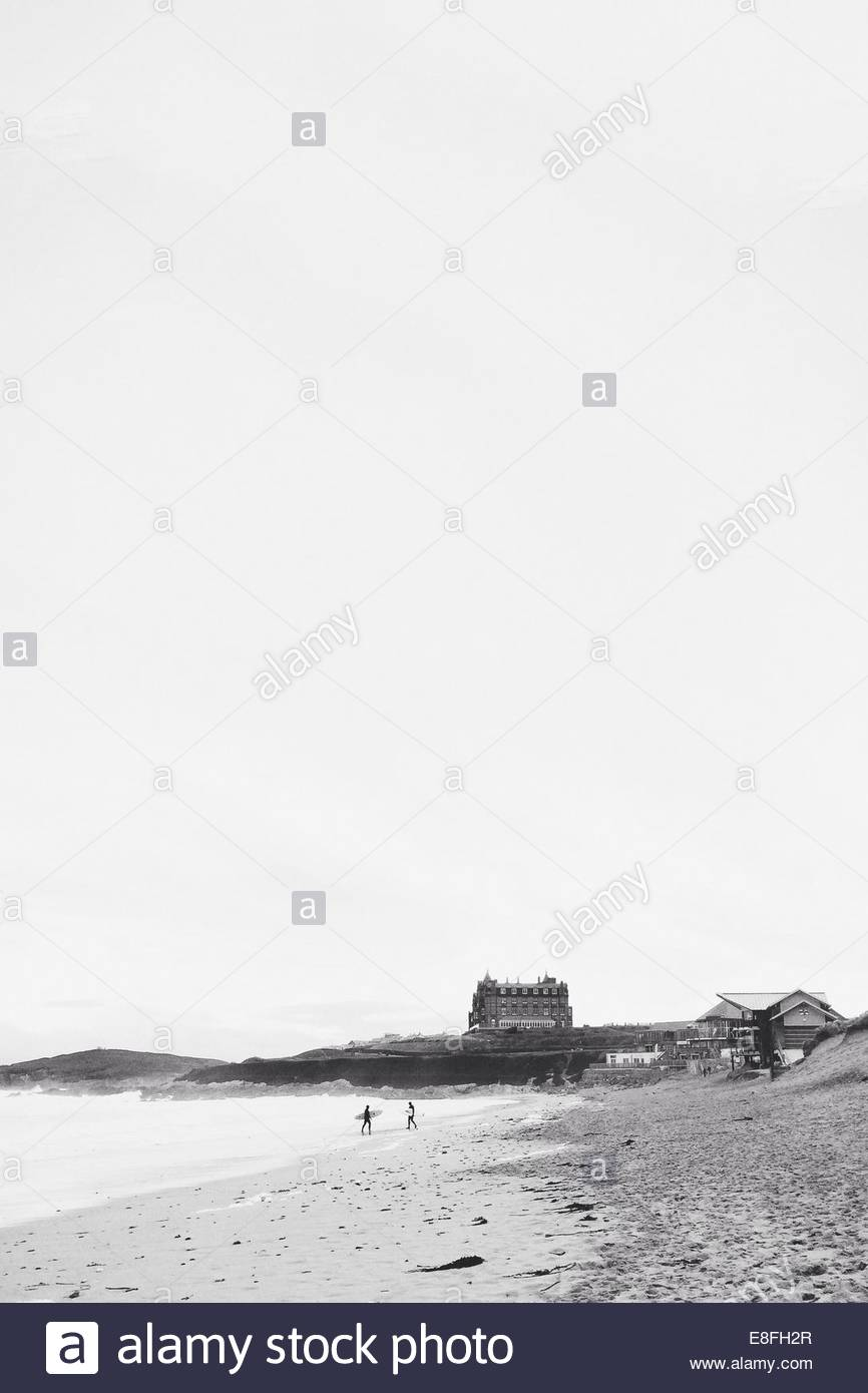 United Kingdom, Cornwall, Newquay, Surfers leaving Fistral beach with Headland hotel behind them - Stock Image