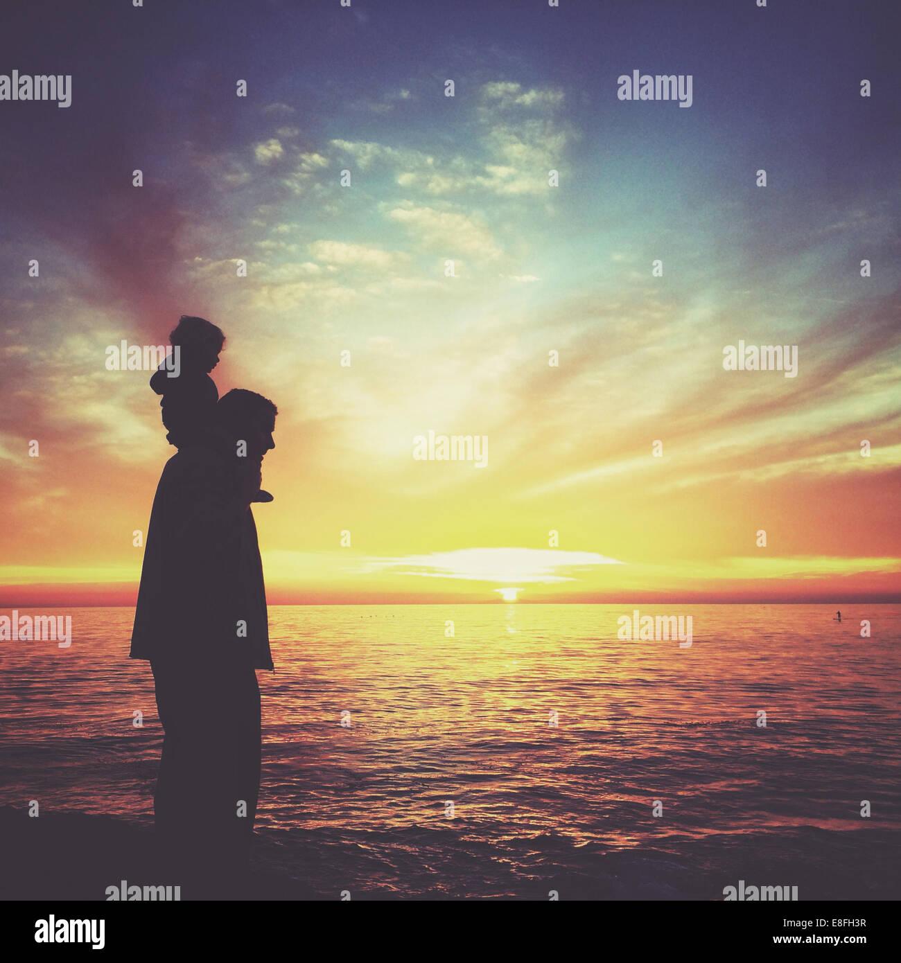 Silhouette of a boy sitting on his father's shoulders, Laguna beach, Orange County, California, USA Stock Photo
