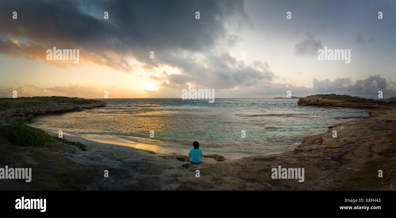Woman watching sunrise near Devil's Bridge, Antigua, Caribbean - Stock Image