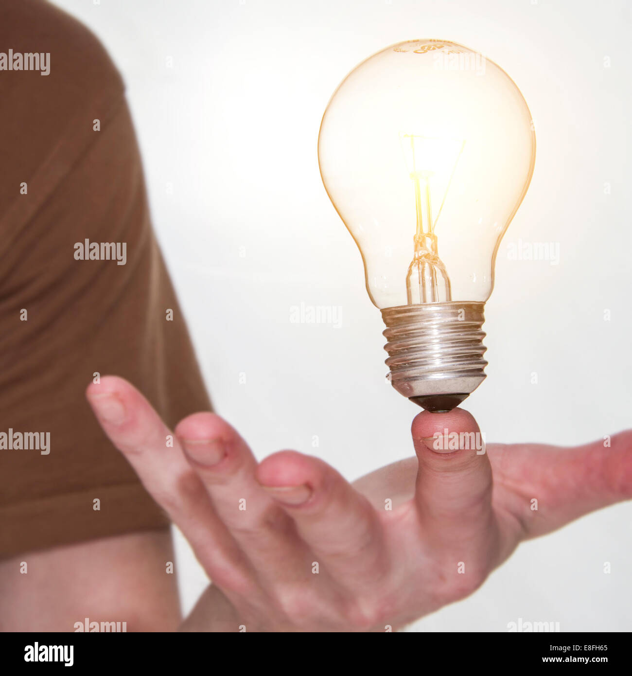 Man holding a lightbulb on his finger Stock Photo