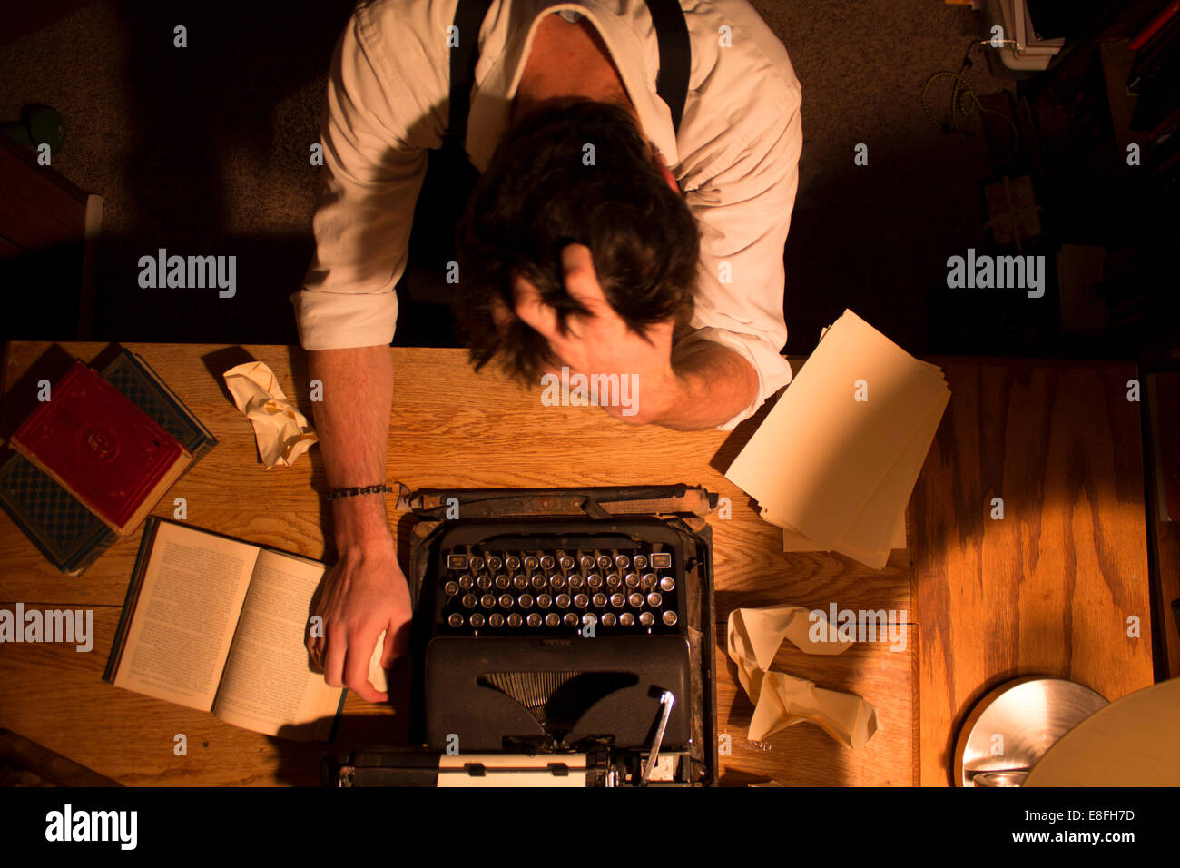 Man sitting at desk with writers block - Stock Image
