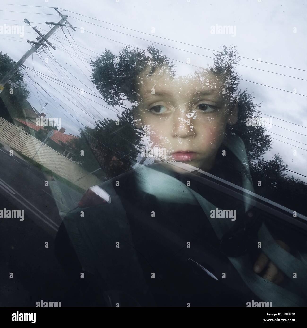 Boy sitting in car seat looking through window - Stock Image