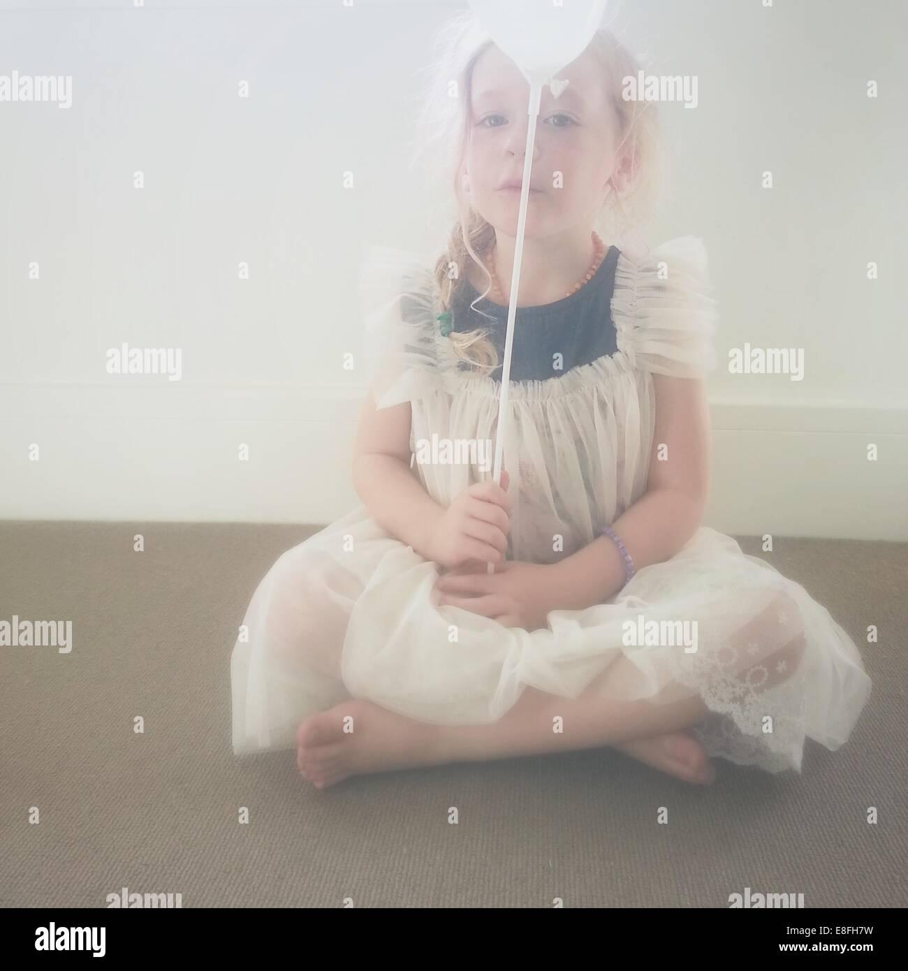Girl sitting cross-legged with a balloon - Stock Image