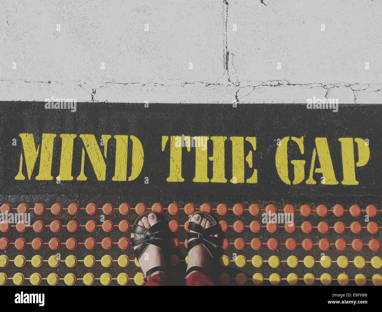 Standing by a mind the gap notice - Stock Image