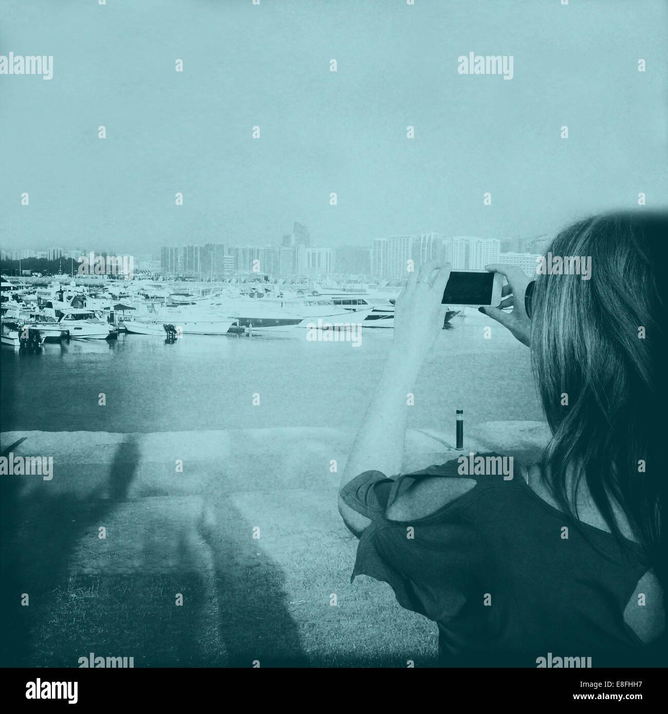 United Arab Emirates, Abu Dhabi, Woman taking photograph on phone - Stock Image