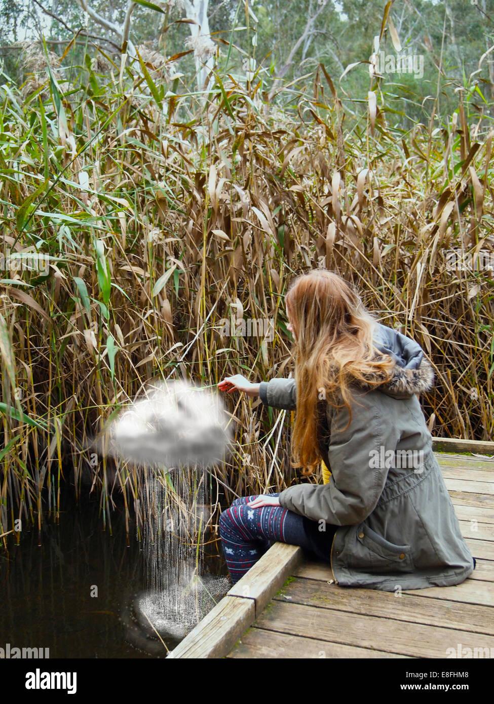 Woman sitting on jetty making rain cloud - Stock Image