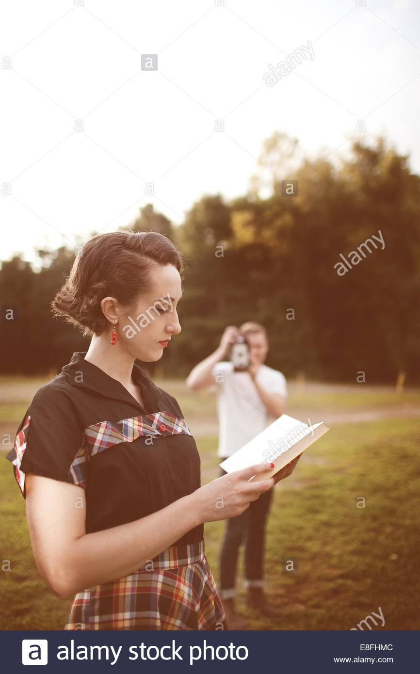 Young man taking photograph of woman reading book - Stock Image