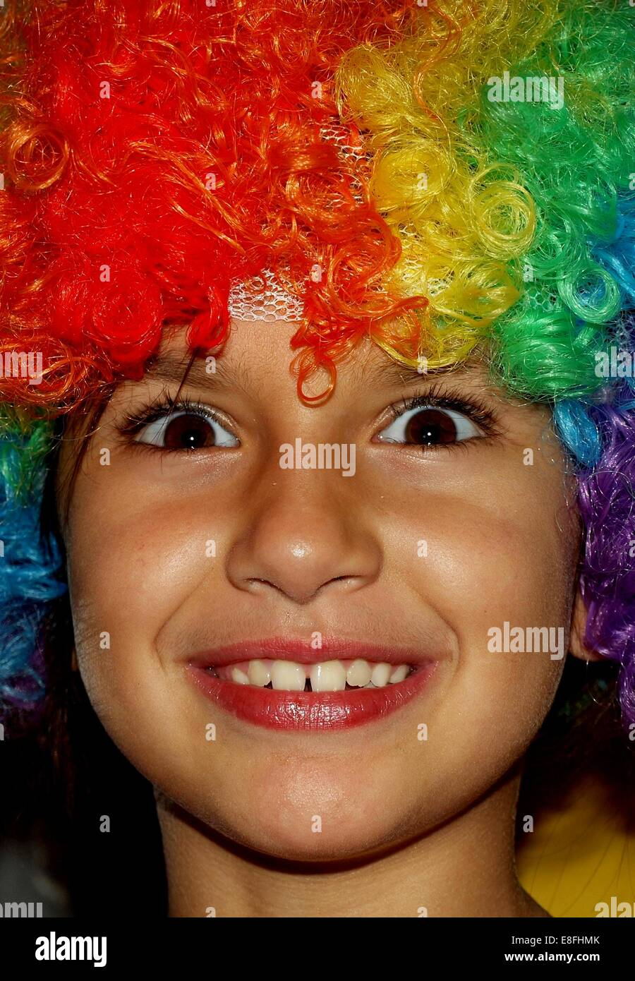 Girl wearing a multi-colored wig - Stock Image