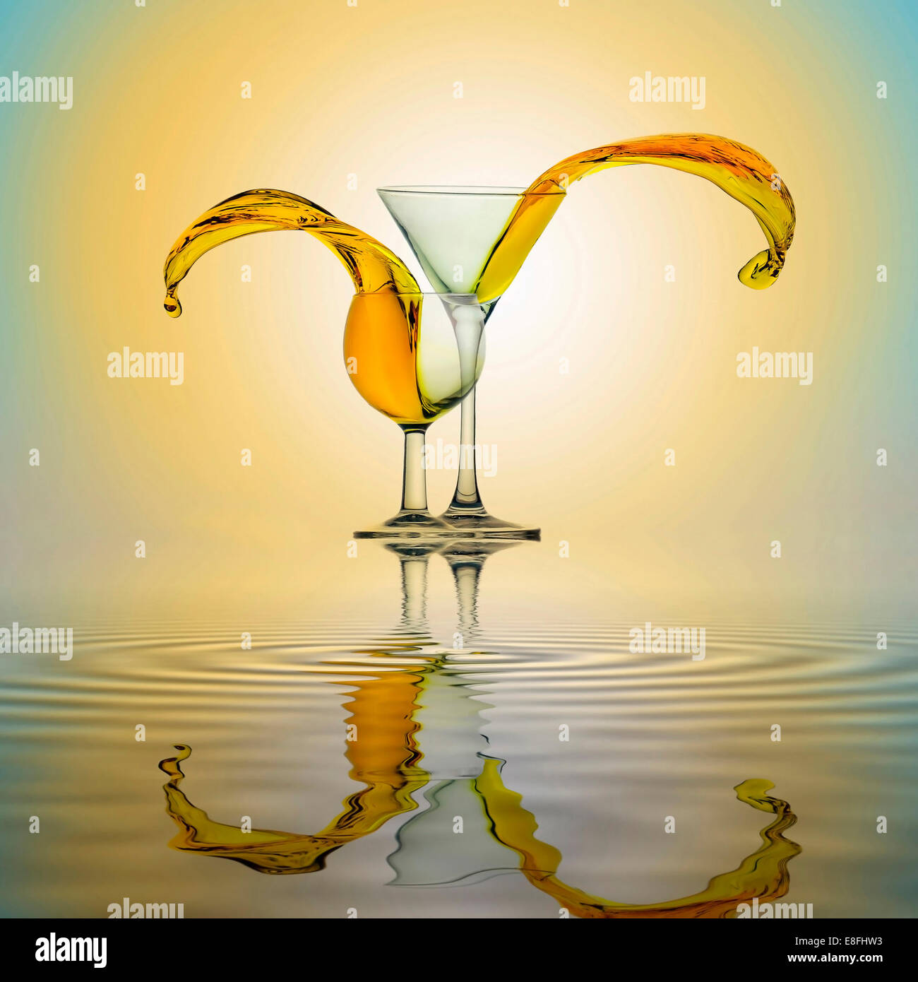 Yellow water splashing from two glasses standing side by side on water surface - Stock Image