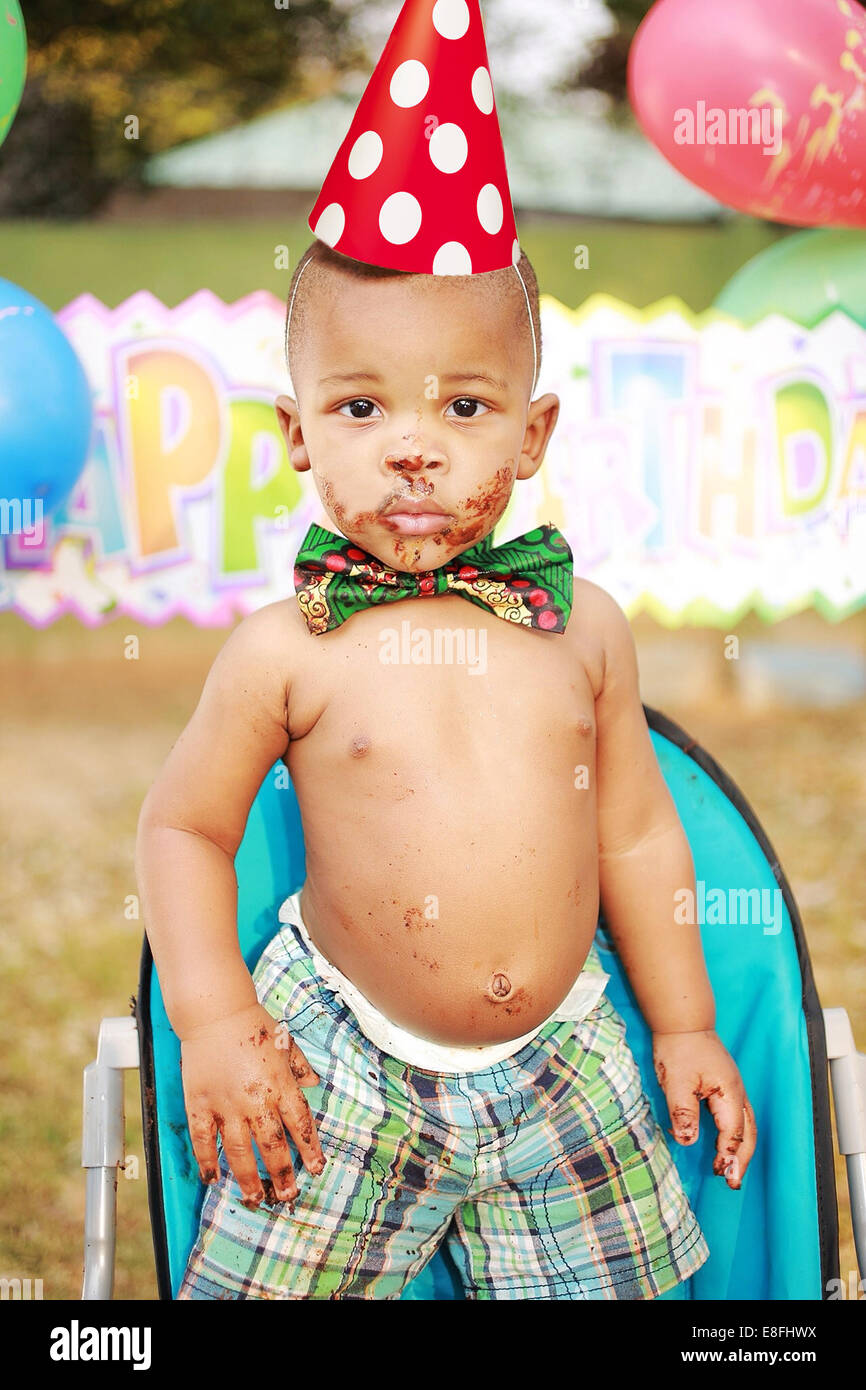 Boy at a birthday party with chocolate cake on his face - Stock Image