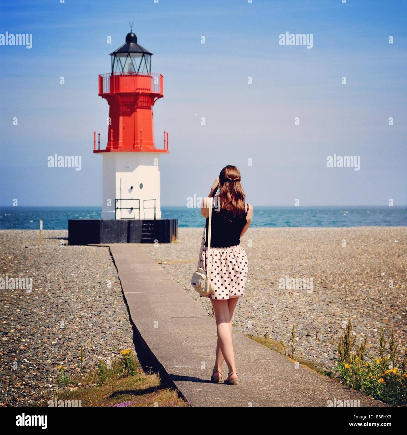 Woman photographing lighthouse, Isle of Man, England UK - Stock Image