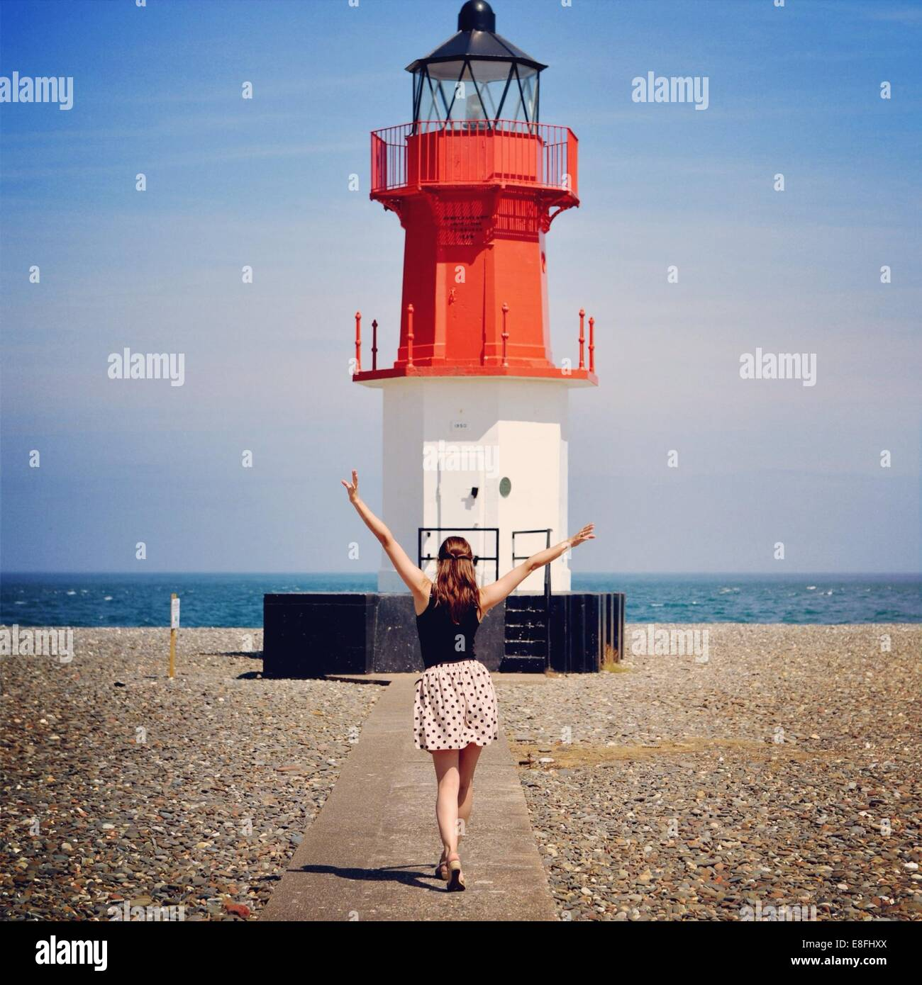 Woman standing in front of lighthouse - Stock Image