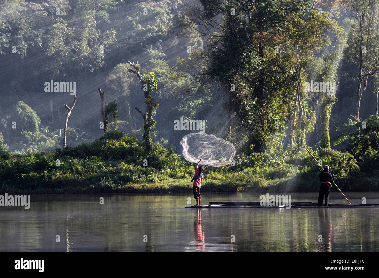 Indonesia, West Java, Karawang, Situ Gunung, Man throwing fishing net into water Stock Photo