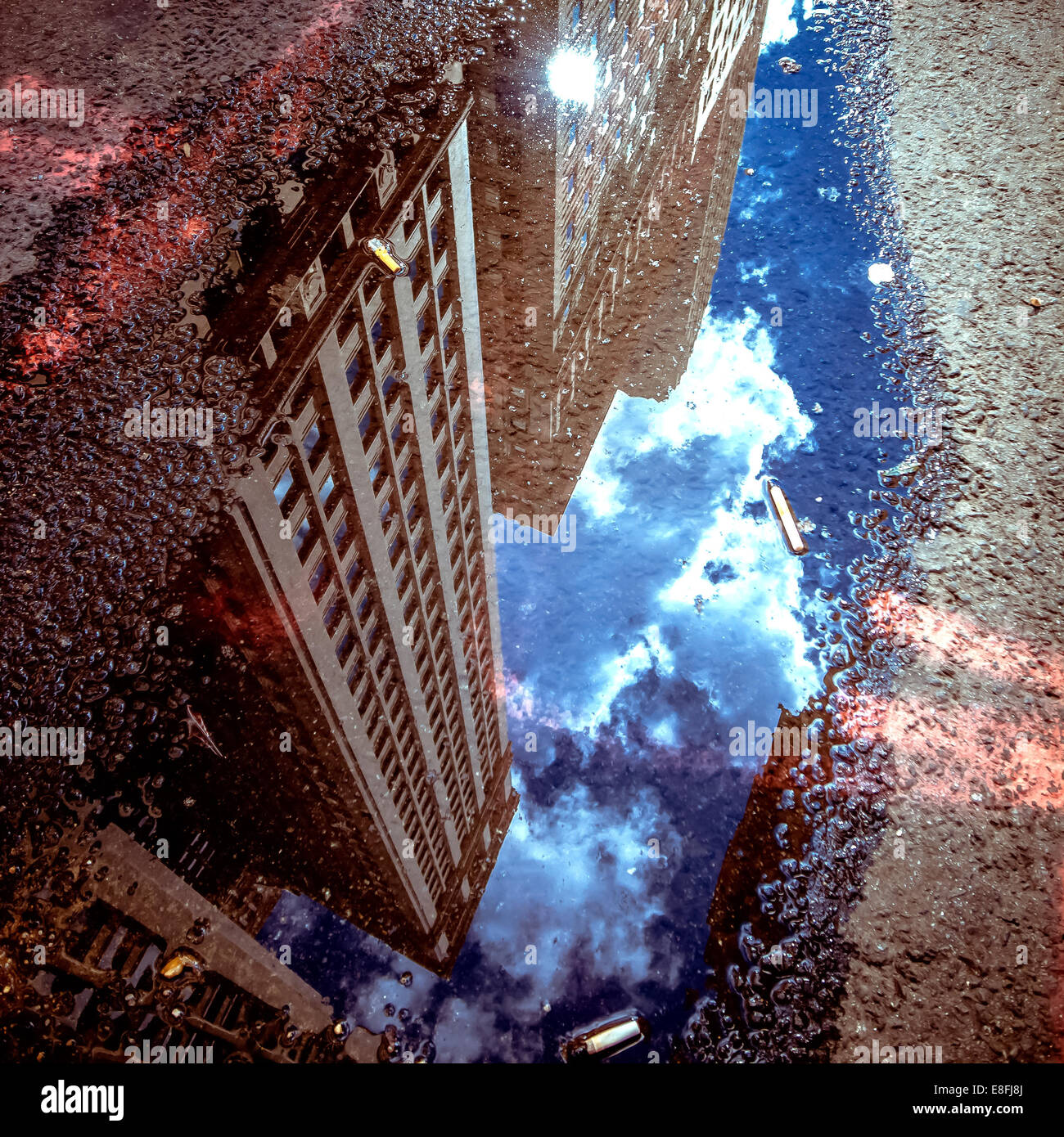 Skyscraper reflections in puddle, New York, America, USA - Stock Image