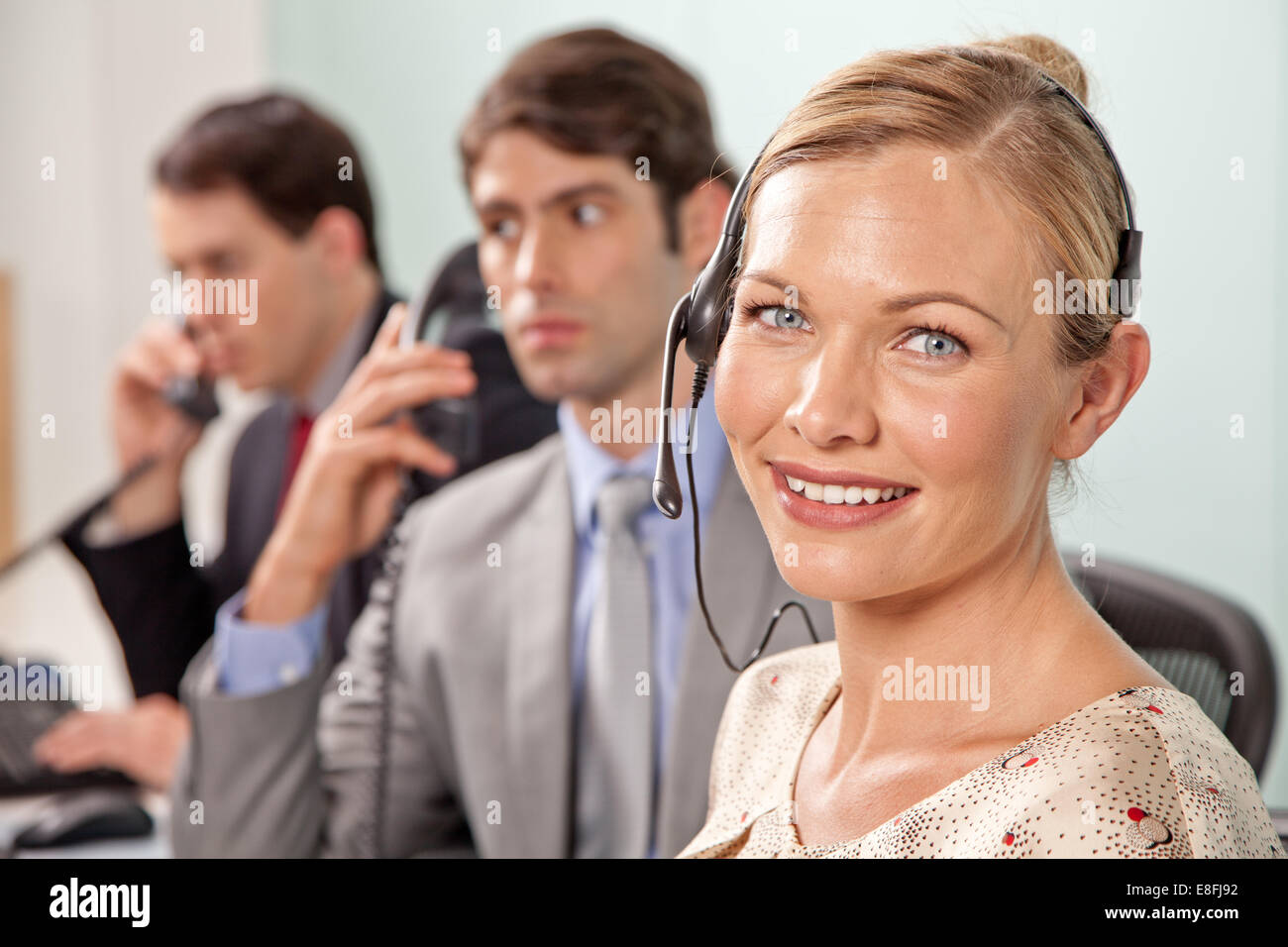 Young woman with phone headset in office with coworkers in background - Stock Image