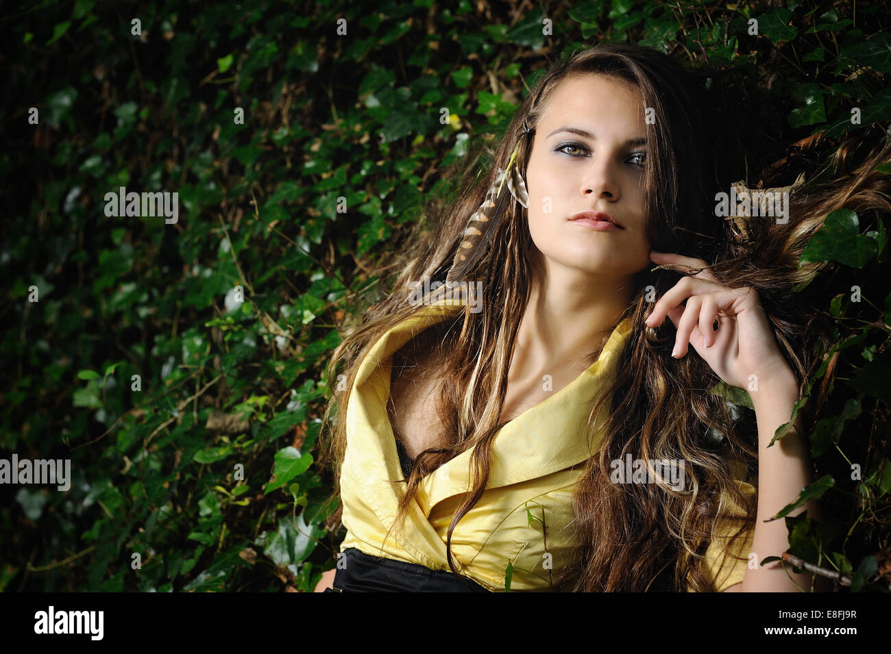 Portrait of woman with yellow dress surrounded by ivy - Stock Image
