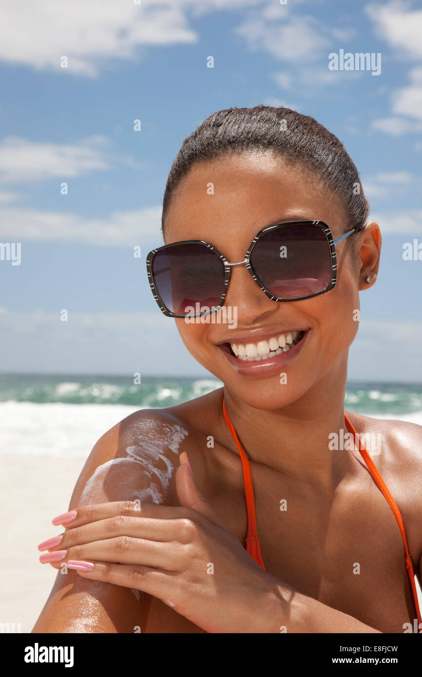 Portrait of smiling woman applying suntan cream, Cape Town, South Africa - Stock Image