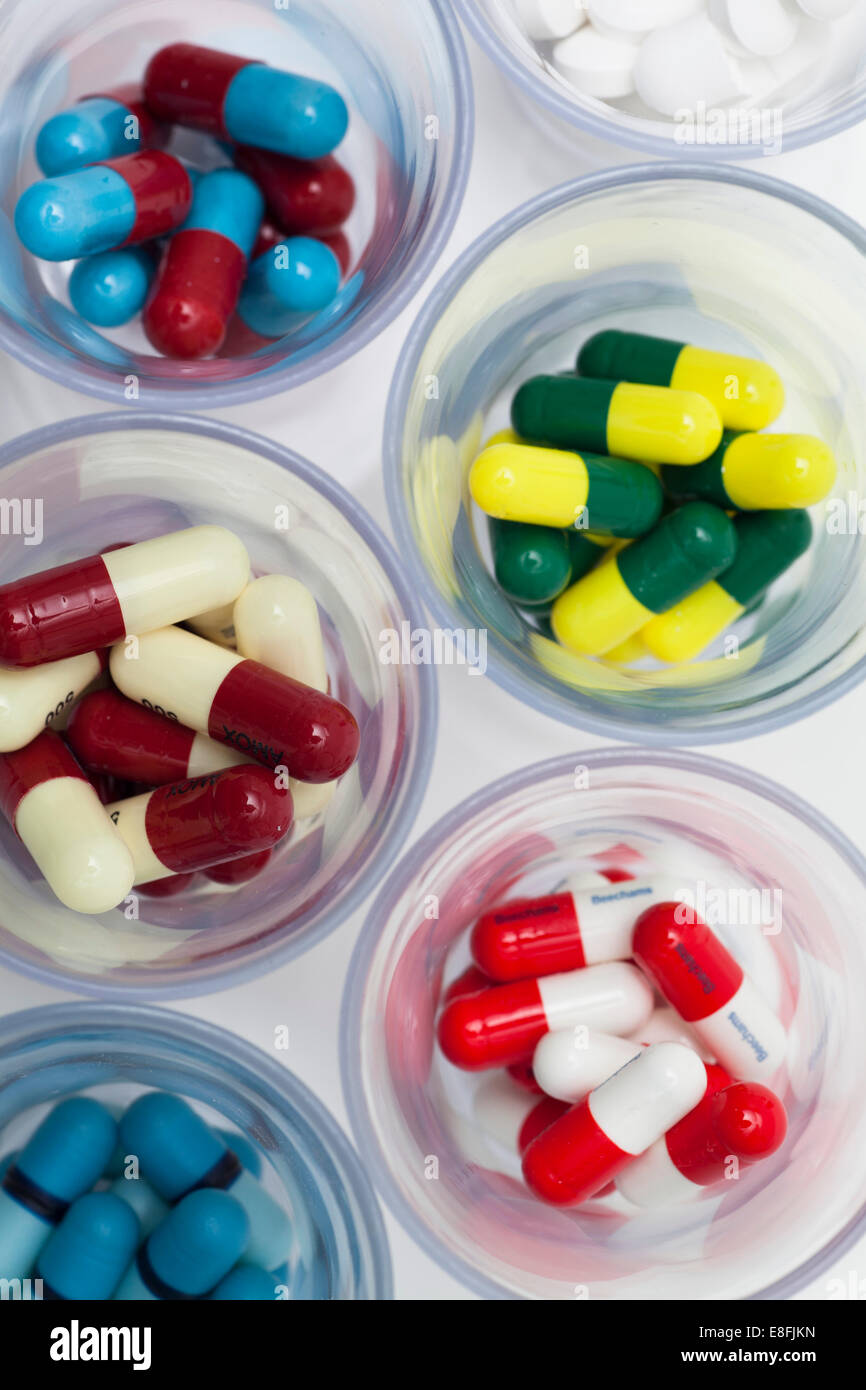 Glass bowls with multi-colored pills - Stock Image