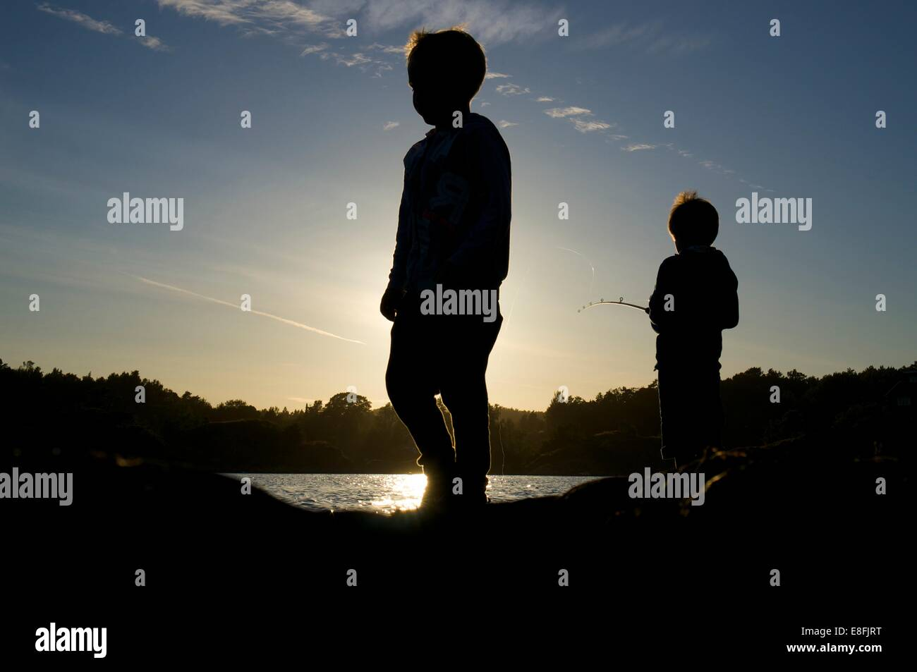 Silhouette of two boys fishing at sunset, Tromoy, Arendal, Norway - Stock Image