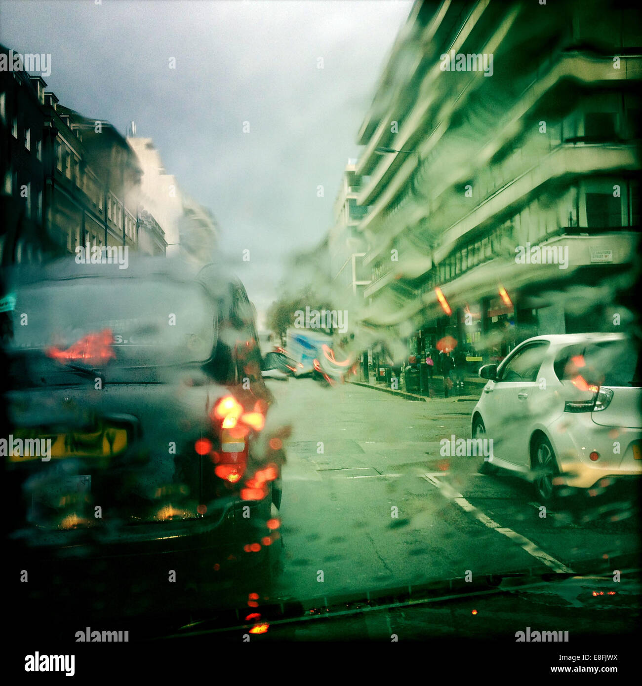 UK, London, Westminster, Knightsbridge, Taxi and car in wet weather - Stock Image