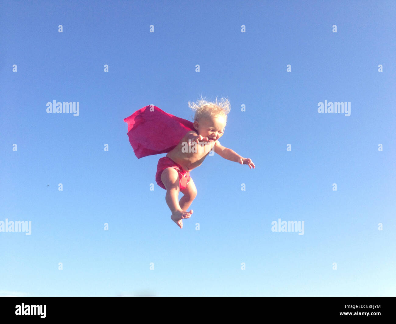 Baby boy dressed as a superhero mid air - Stock Image