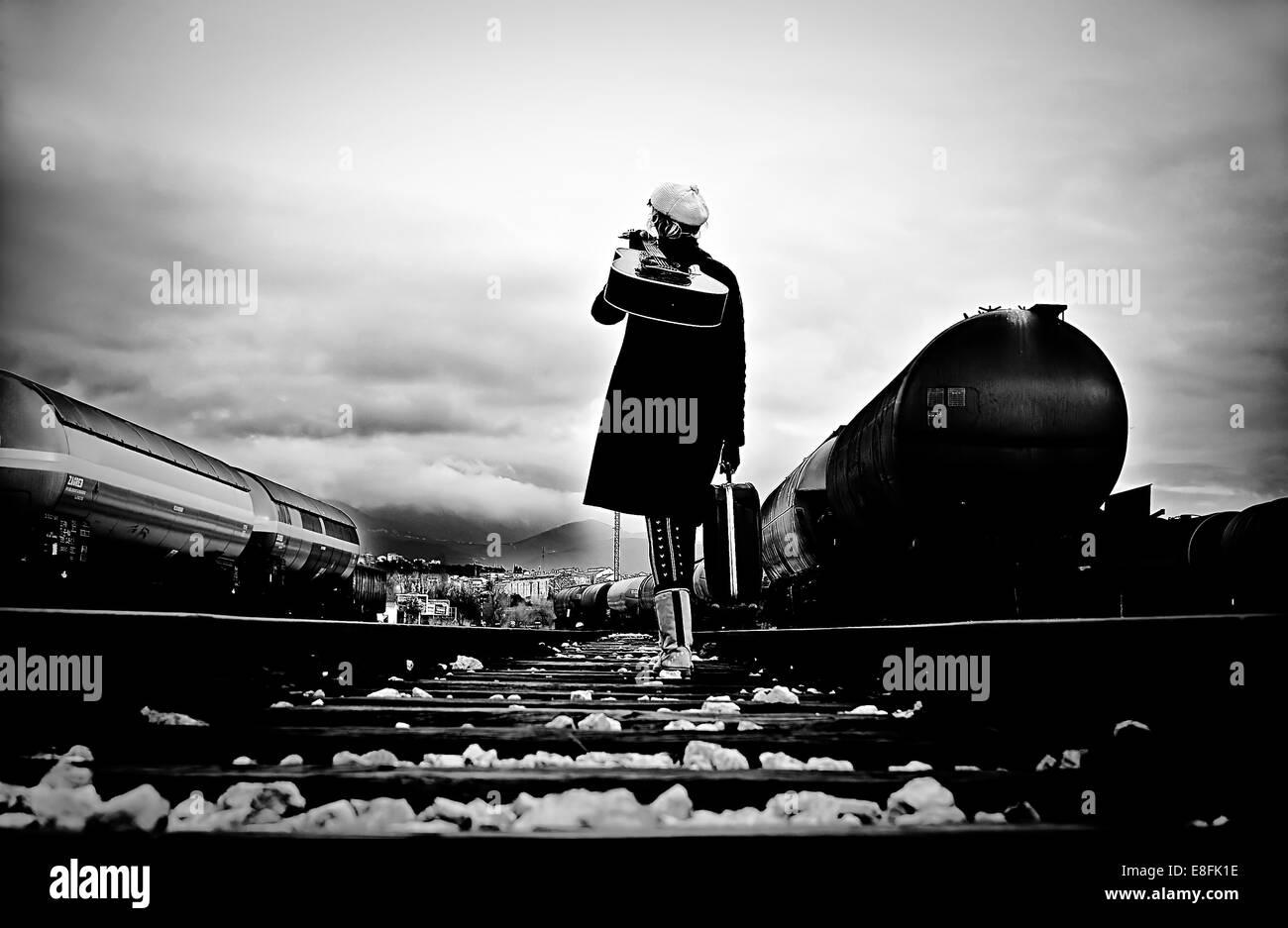 Woman walking along train tracks carrying a guitar, Croatia - Stock Image