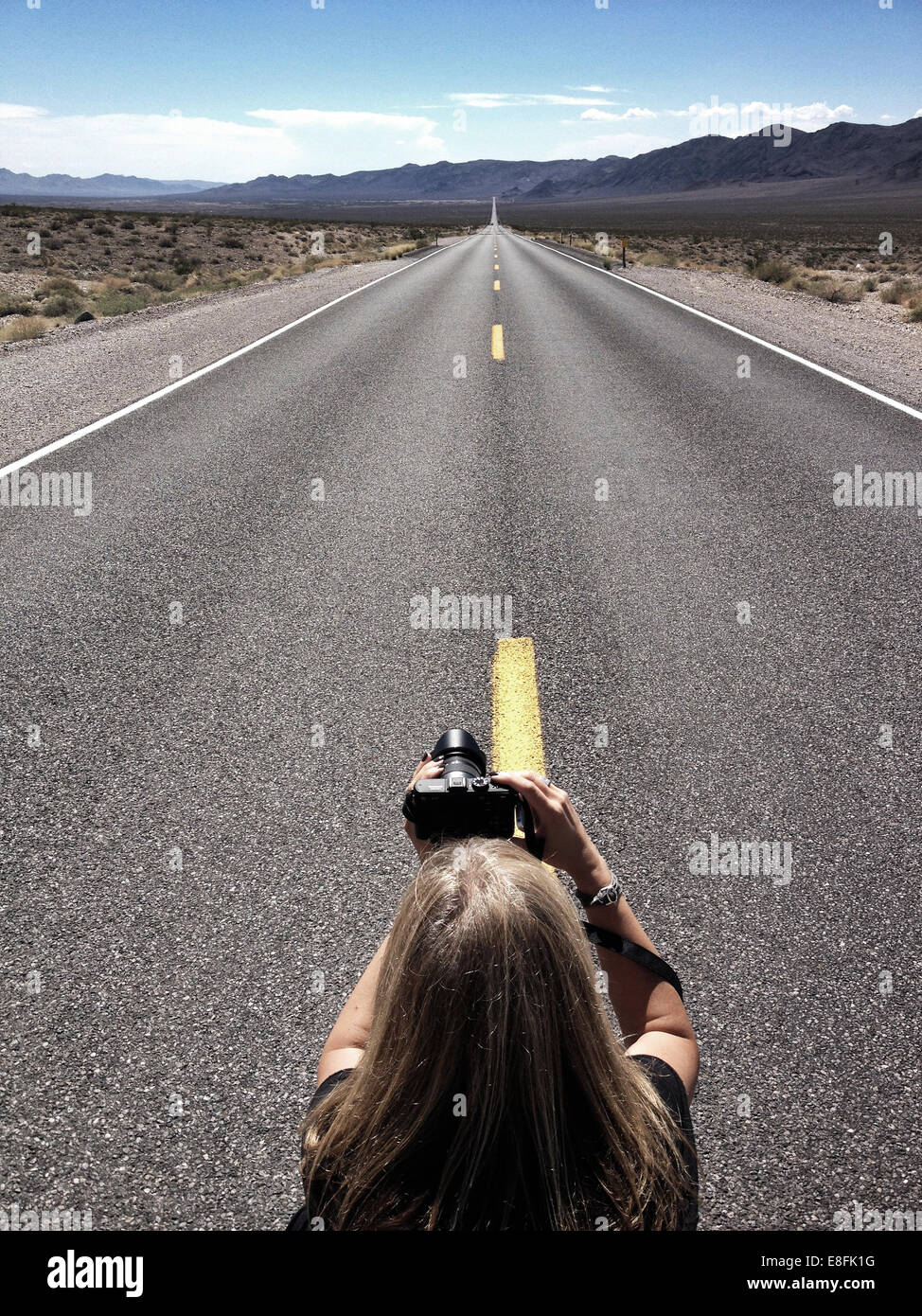 Woman taking photograph of empty road, California, America, USA - Stock Image