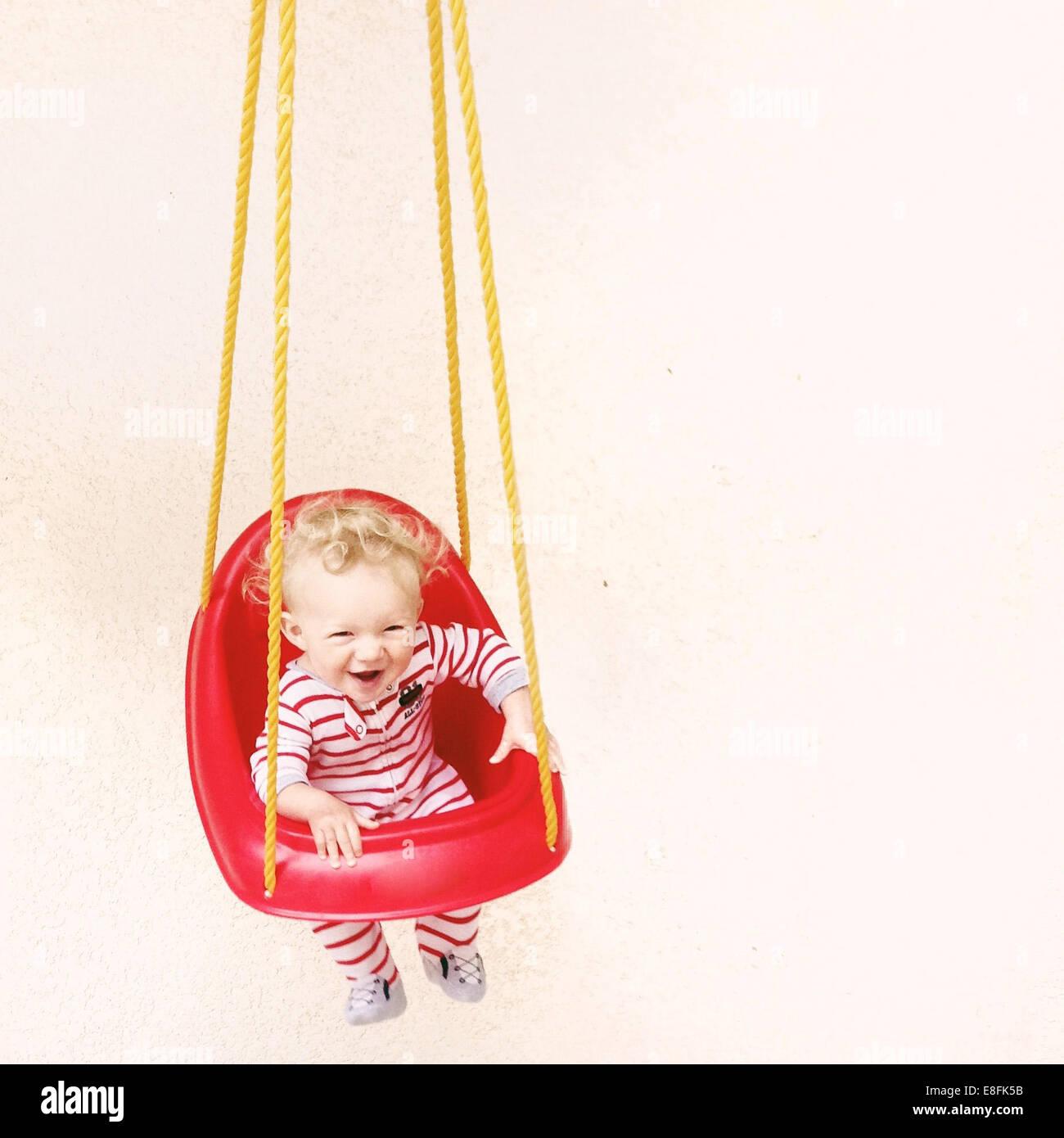 Boy in pyjamas sitting in a swing - Stock Image