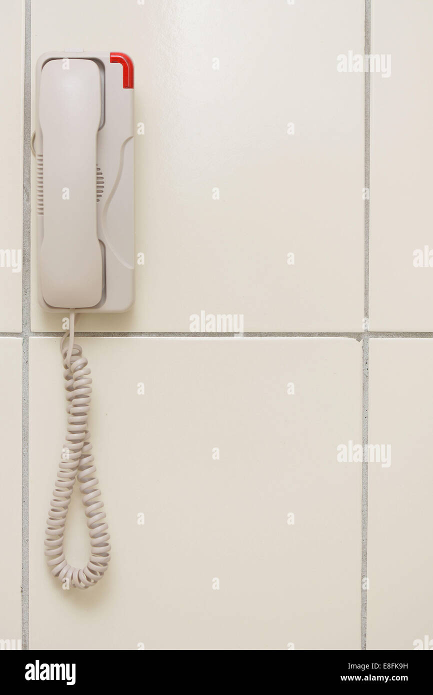 Malaysia, White phone hanging on wall - Stock Image