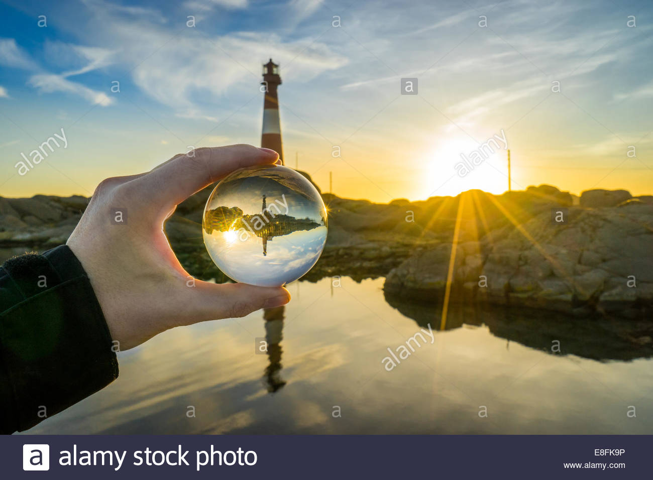Norway, Rogaland, Eigeroy lighthouse and sunset seen through crystal ball - Stock Image