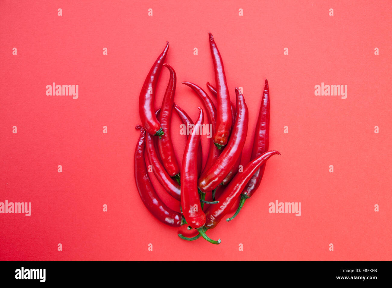Red chill peppers arranged in the shape of a flame - Stock Image