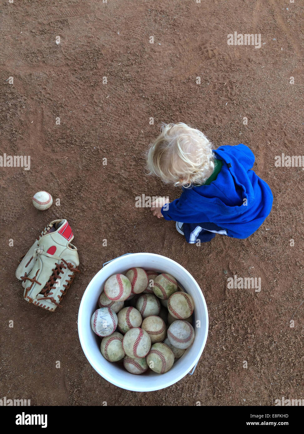 Boy collecting baseball balls in a ball bucket - Stock Image