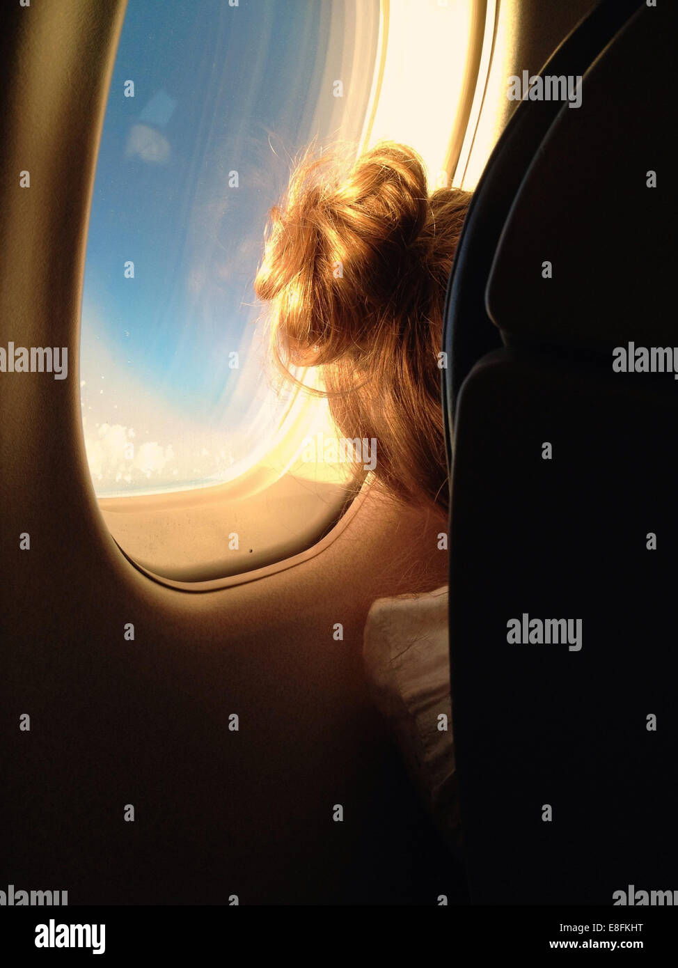 Rear View Of A Girl Sitting In A Plane - Stock Image