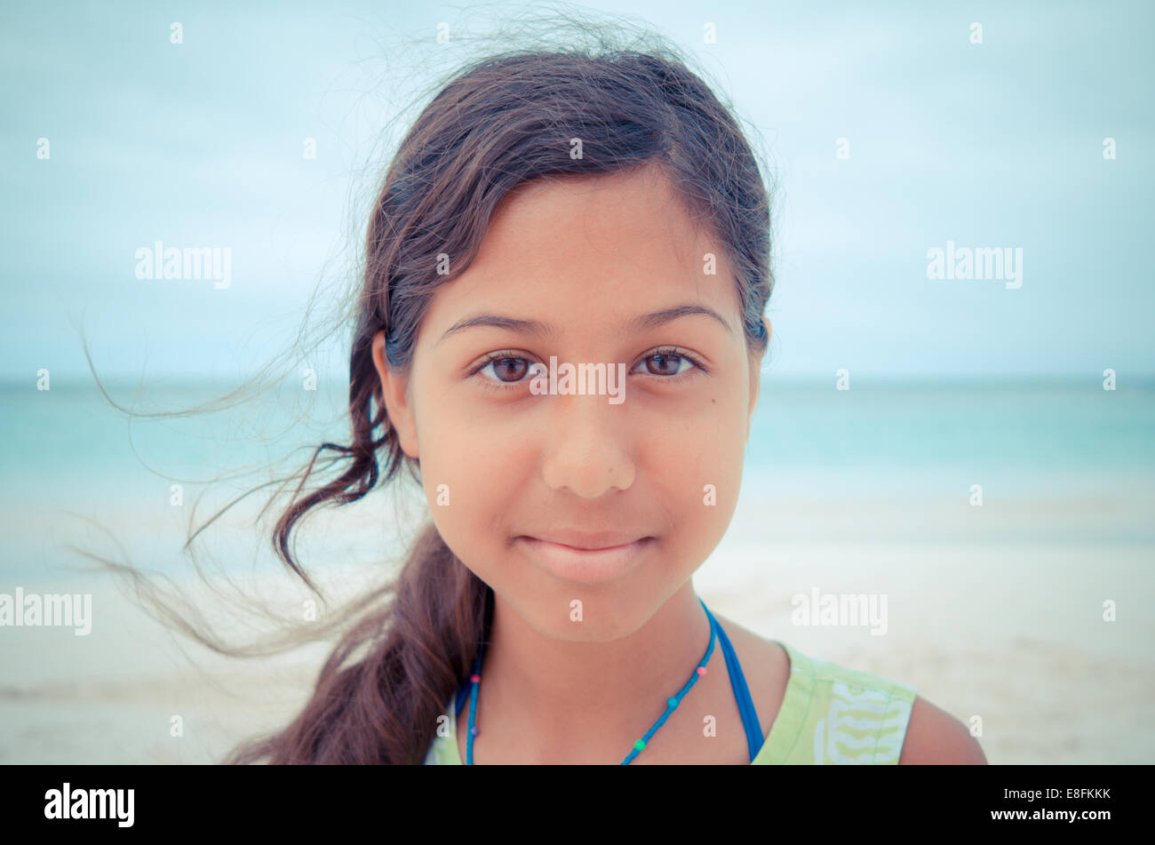 Portrait of a smiling girl standing on a beach, Antigua, Caribbean - Stock Image