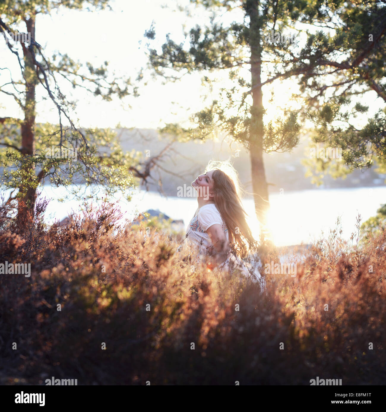 Young woman walking by lake - Stock Image