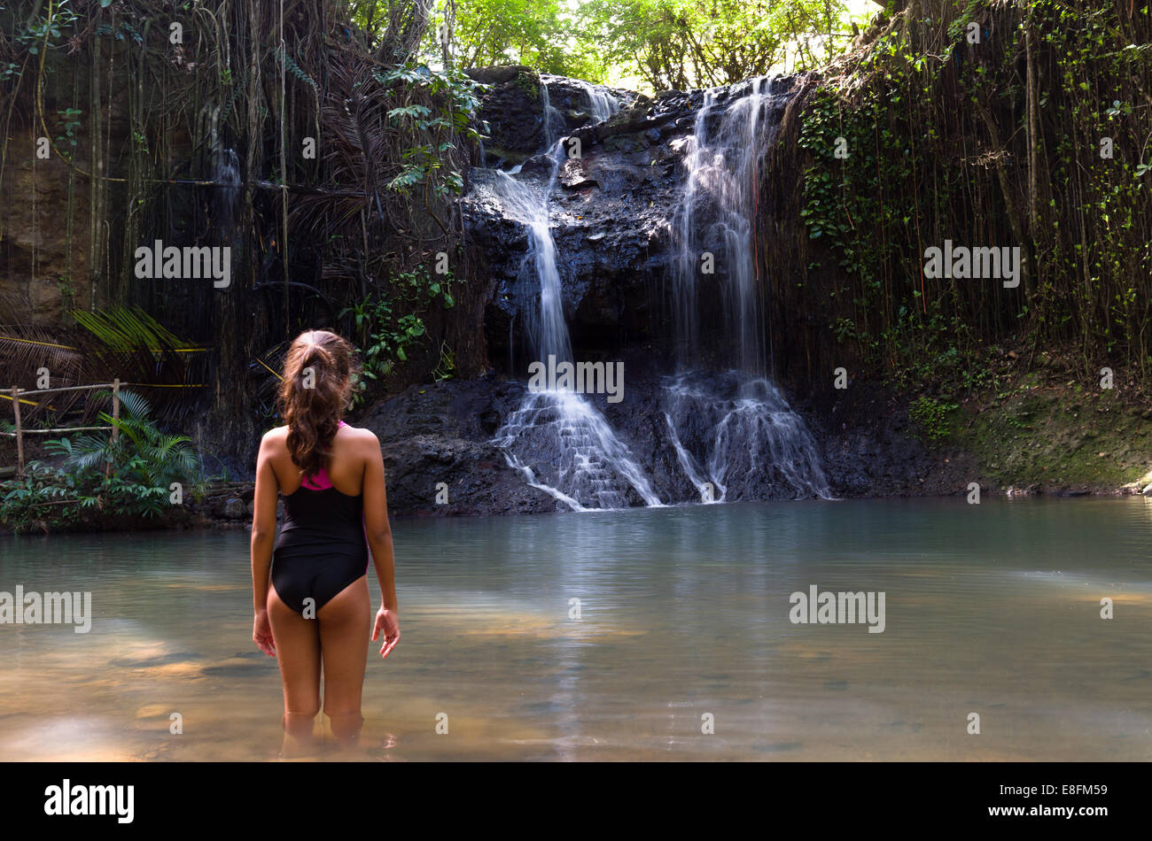 Girl standing in lake looking at waterfall, Caribbean Stock Photo