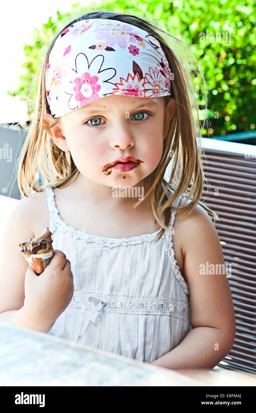Girl eating ice cream with chocolate mess around mouth - Stock Image