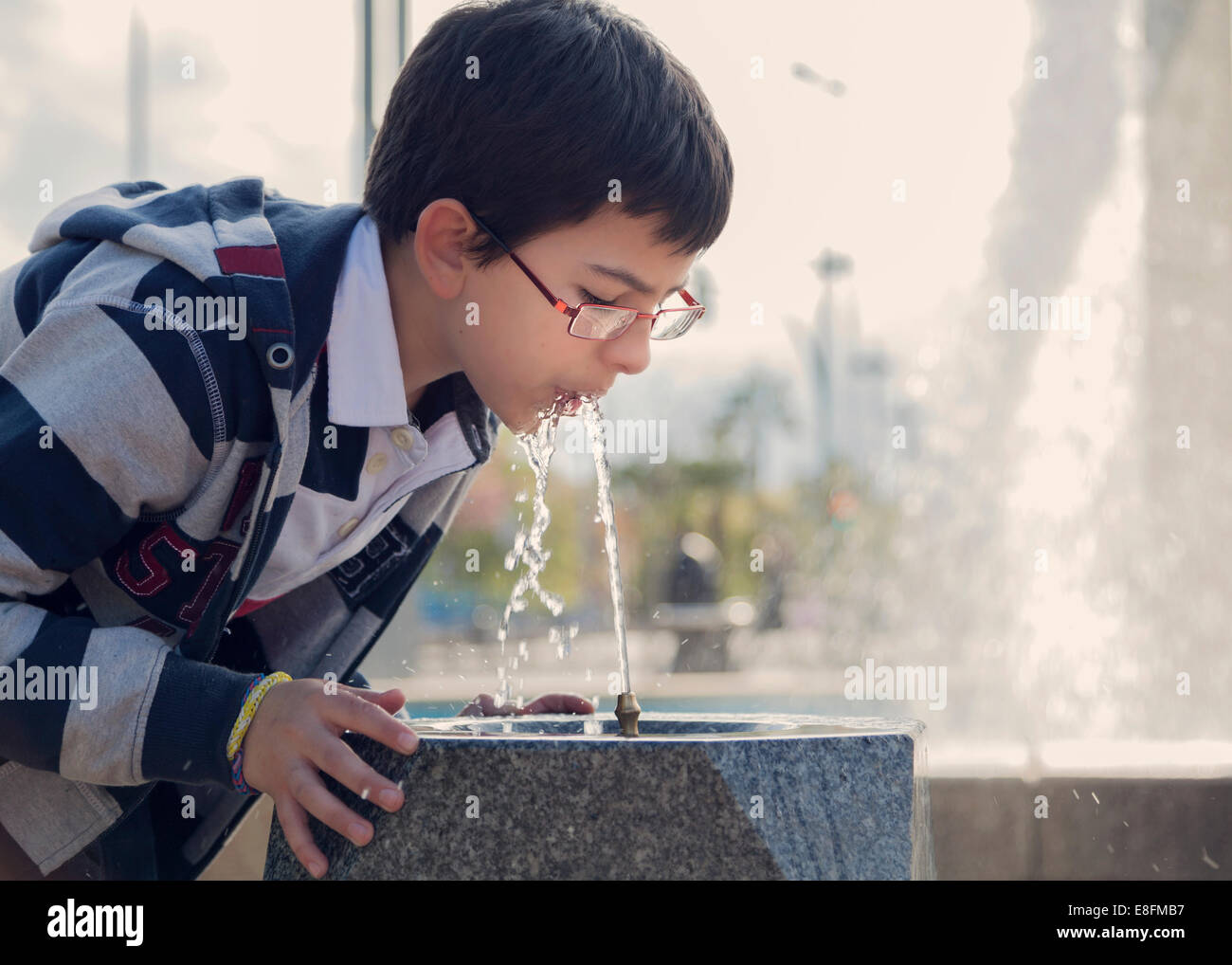 Spain, Cordoba, Boy (12-13) drinking water from fountain in park - Stock Image
