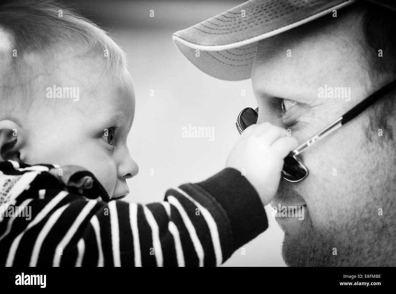 Baby boy playing with his father's sunglasses - Stock Image