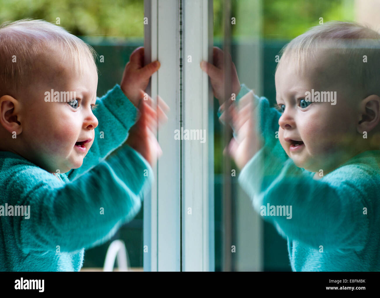 Baby boy playing with his reflection in window - Stock Image