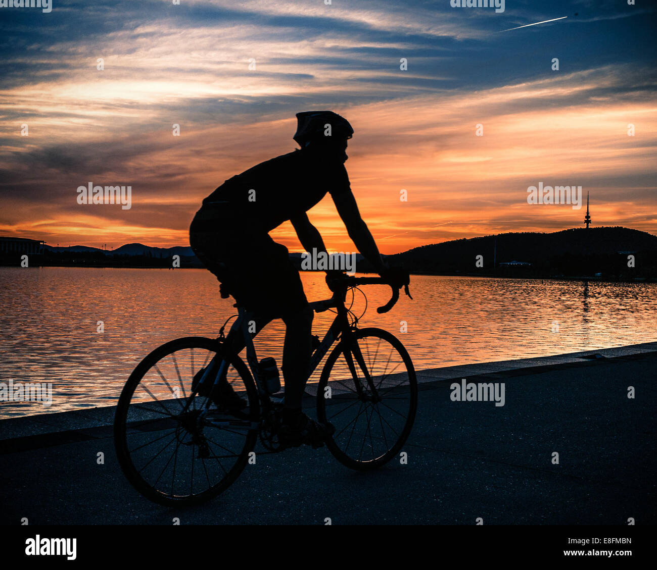 Silhouette of cyclist at sunset near Lake Burley Griffin, Canberra, Australia - Stock Image