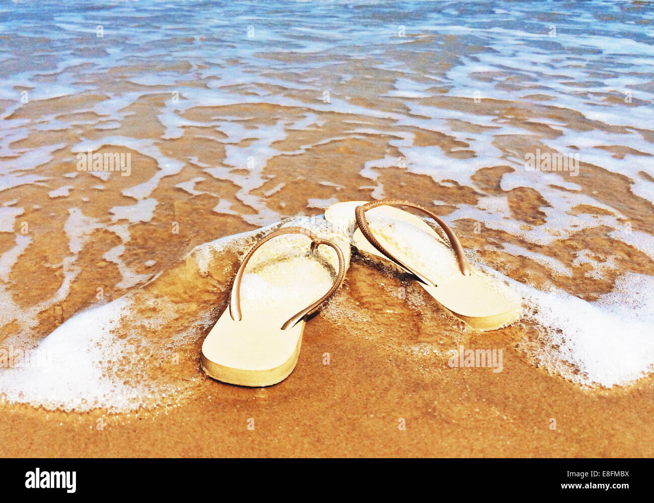 Flip flops on beach in surf - Stock Image