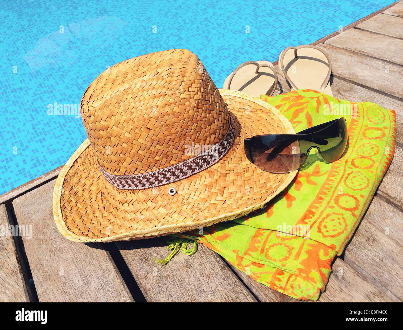 Straw hat, sunglasses, flip flops and sarong on wooden deck by swimming pool - Stock Image