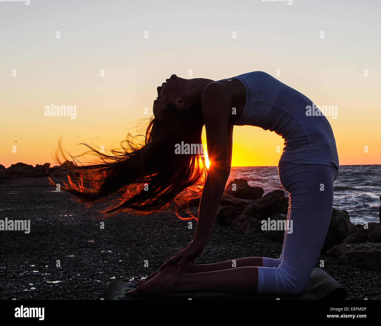 Woman practicing yoga on beach at sunset - Stock Image