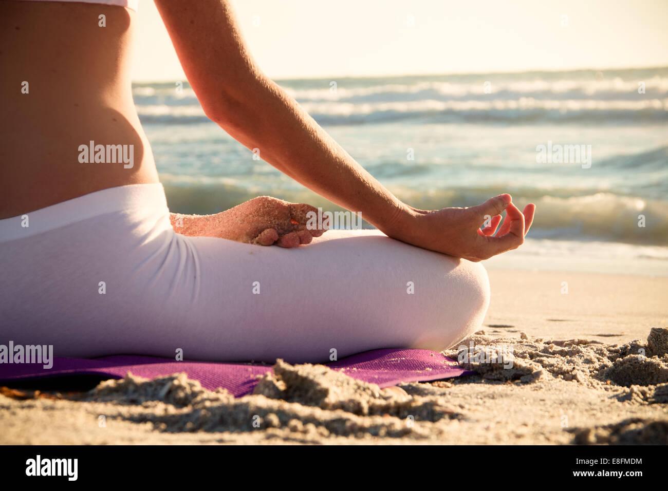 Woman practicing yoga on beach - Stock Image