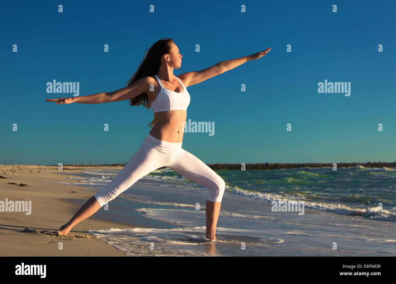 Woman practicing warrior 2 yoga pose on beach Stock Photo